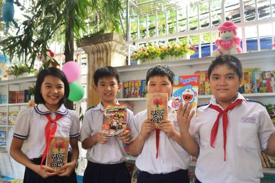 "The Quan (2nd from the right) and his friends in the newly built library, which is the pupils' initiative to replace the old one in Nguyen Viet Xuan Primary School. ""This is the perfect location in the school yard for reading, quiet, close to the nature, and a lot of sun shine! What do you like about reading? I can make friends with books and I can be a librarian in the future! What advice would you give to other people if you are a librarian? Don't damage books. Don't tear the pages. It's not an easy job, you know! What is difficult about being a librarian? Being busy keeping an eye for the pupils who want to borrow books"" Photo credit: An Ha Nguyen"